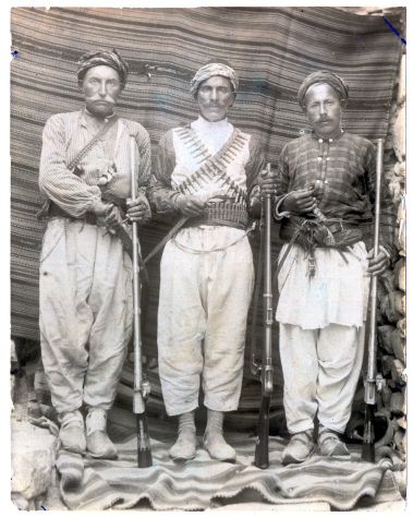 "Ward's caption on reverse: ""Picture of three Koords. Notice the armament. These Koords are mountaineers & enjoy a fight better than eating. This is the way in which they like to pose for a picture."" Chambers in ""Yoljuluk"": ""The Koords appealed to me in many ways, a race of fine physique, many of them tall and of handsome appearance, with a vigorous swing that would naturally characterize mountaineers who roam at pleasure over hill and valley."""