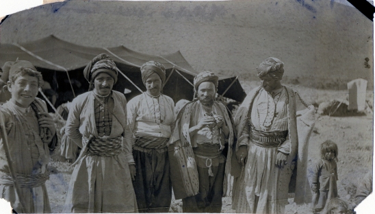 "Ward: ""Four Koords – same as in Koordish encampment.  Notice Koord with spyglasses, another with cartridges in belt, little girl at right, Armenian boy, a guard, at left.""  Chambers: ""They are generously hospitable, bountiful hosts with a sense of the sacred rights of the guest who is safe while within his host's precincts.  However, their sense of the rights of property is not developed to such an extent that the guest might not be relieved of his possessions once outside the territory of his host.  They maintain the tribal system."""