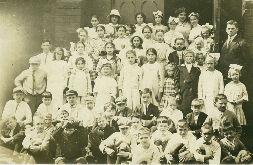 Several dozen children pose together on a staircase. An adult man in a suit stands to the right. A wooden door behind the group stands open.