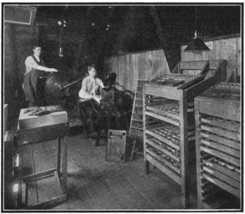 A boy stands at a small galley press, while a young man stands behind him at a full printing press. Two cabinets of loose type stand against the right wall of the small room.