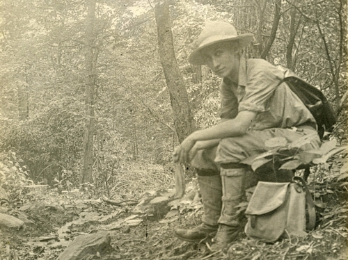 A young woman wearing a camp shirt, khaki pants, and field boots, sits on a tree stump in the woods.