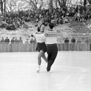 A crowd sits on a grassy hill, and watches two figure skaters perform a dance on the ice rink. The pair wear matching sweaters, and are holding hands with their left arms extended.