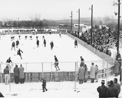 Two ice hockey teams skate on the ice. A crowd watches, with people sitting in bleachers or standing around the rink on snow-covered ground.