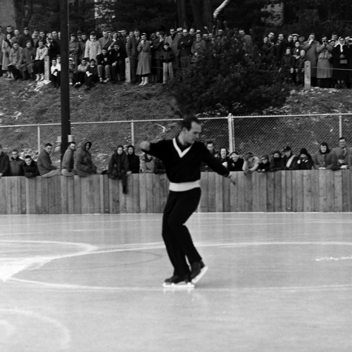 A male ice skater, dressed in black, lifts his foot and extends his arms as he twists his body to the right. Spectators in winter coats stand behind the wooden fence at the rink edge, and on the hill rising behind the rink.