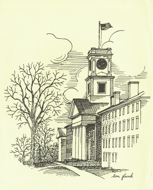 A four-story brick building with chimneys stands next to a chapel fronted by columns. An American flag flies from the clock tower. The trees in front of the buildings are bare, and the sky is full of large puffy clouds.