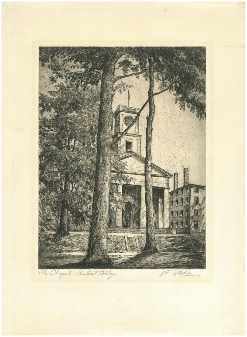 Behind two large trees, A tall square clock tower tops a brick chapel building with four plain columns.