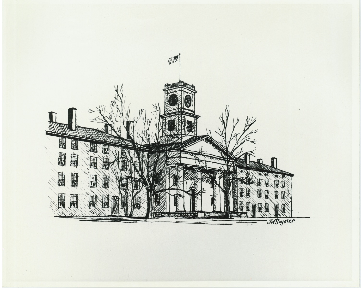 Two four-story brick building with chimneys stand on either side of a chapel fronted by columns. An American flag flies from the clock tower. The trees in front of the buildings are bare.