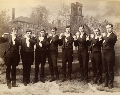 A photograph of eight students in formal wear in front of a painted backdrop of Johnson Chapel. The students appear to be holding invisible flutes.