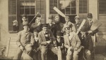 Photograph of a group of students holding a variety of implements including, an ax, paddles, boards, rope, brooms, and sticks. Students are posed in front of a house.