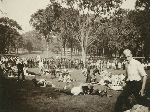 Photograph of clusters of students rolling on the ground in fisticuffs, behind them is a crown of onlookers behind a rope.