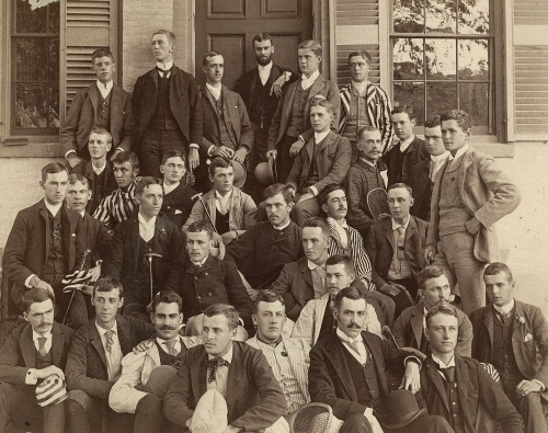 Photograph of a large group of young men in a variety of fashions. Most of the men are looking off the side of the picture with sultry expressions.
