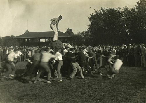 Photograph of a large group of students fighting, surrounded at a distance by a crown of observers