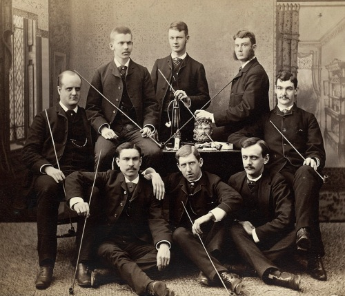 Photograph of a groups of students formally dressed holding very, very long pipes, posed around a table in a photography studio