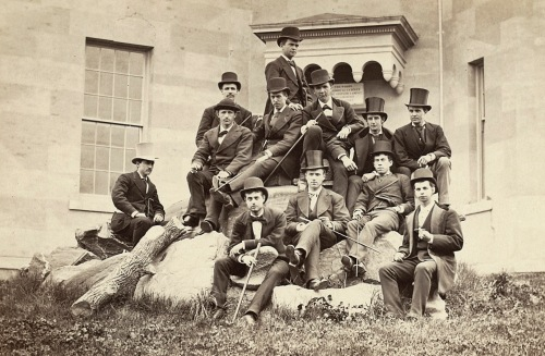 Photograph of a group of students with canes and top hats sitting on a large rock, probably from the 1880s.