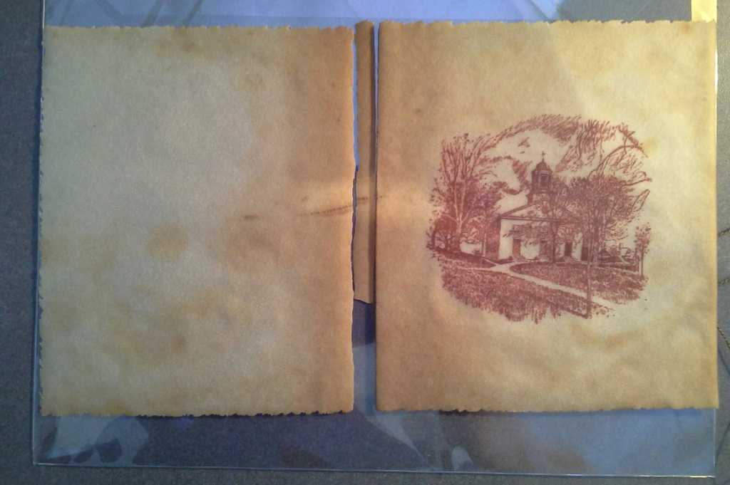A picture of College Hall is printed in purple ink on a light brown piece of material, about 14 inches wide. The piece is broken halfway across, where the material was folded like a book cover.